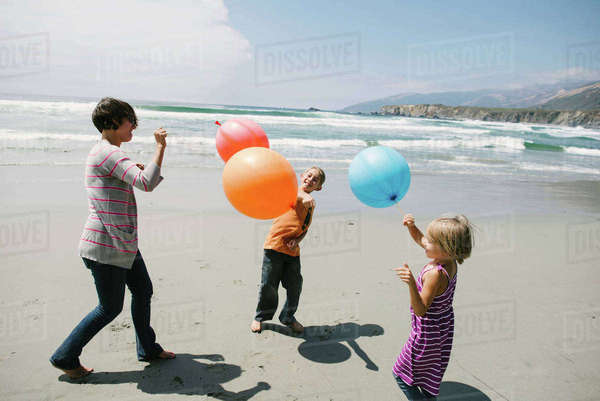 Mother and children playing with balloons while standing on sand at beach Royalty-free stock photo