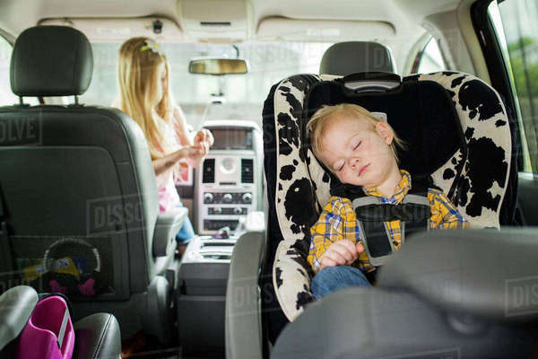 Brother sleeping while sister playing in car Royalty-free stock photo