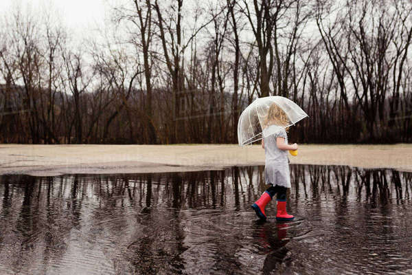 Side view of girl carrying umbrella while walking on puddle during rainy season Royalty-free stock photo