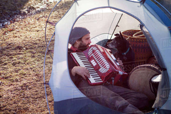Man playing accordion for dog while sitting in tent at campsite Royalty-free stock photo