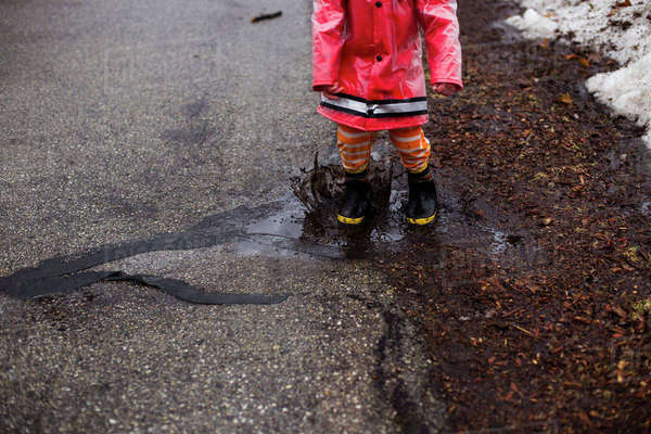 Low section of boy splashing in puddle on street Royalty-free stock photo