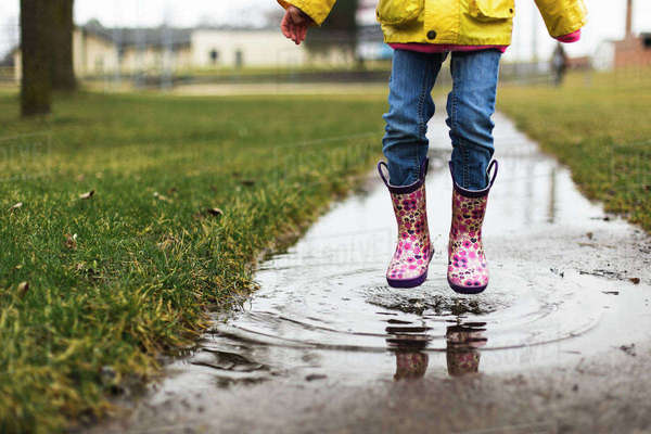 Low section of girl jumping in puddle Royalty-free stock photo