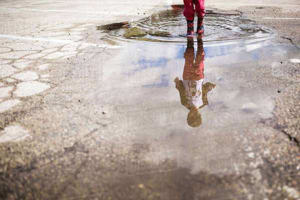 Low section of boy playing in puddle Royalty-free stock photo