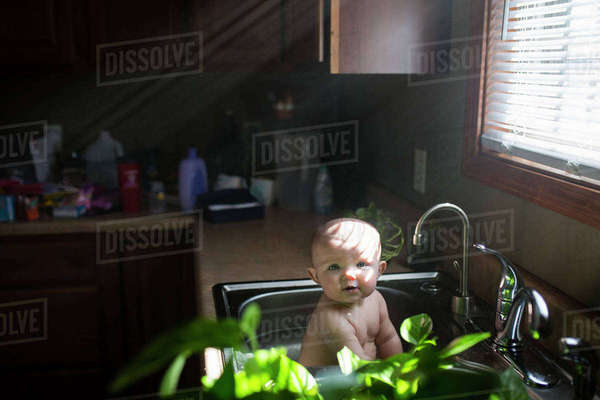 Portrait of cute shirtless baby girl playing in kitchen sink at home Royalty-free stock photo