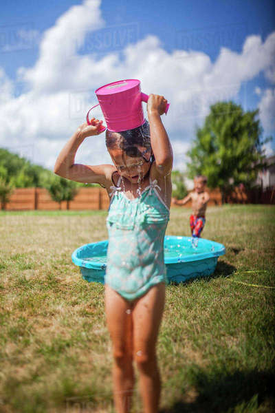 Girl pouring water on head while standing on grassy field at backyard Royalty-free stock photo