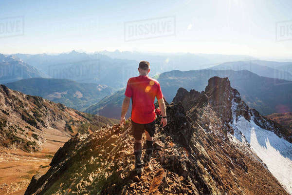 Rear view of male hiker walking on rocky mountains against sky during sunny day Royalty-free stock photo