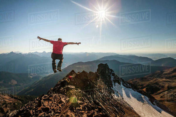 Rear view of hiker with arms outstretched jumping on rocky mountain during sunny day Royalty-free stock photo