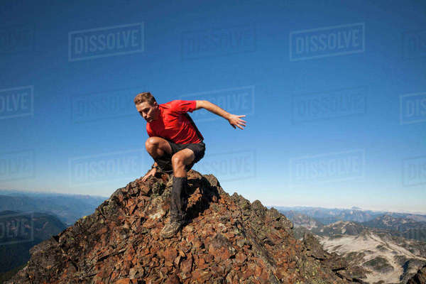 Man moving down from rocky mountain against clear blue sky during sunny day Royalty-free stock photo