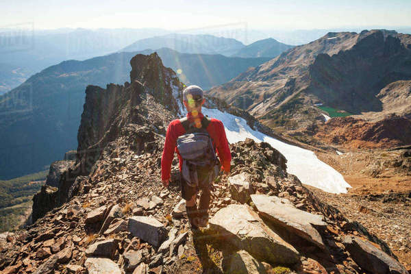 Rear view of male hiker with backpack walking on rocky mountains during sunny day Royalty-free stock photo