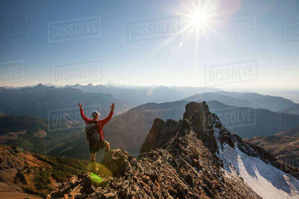 Rear view of male hiker with arms raised standing on rocky mountains during sunny day Royalty-free stock photo