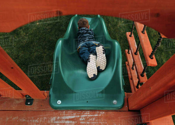 High angle view of playful boy sliding at park Royalty-free stock photo