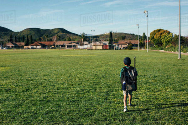 Rear view of boy carrying backpack while walking on grassy field against sky Royalty-free stock photo