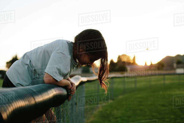 Side view of girl bending over fence at playground during sunset Royalty-free stock photo