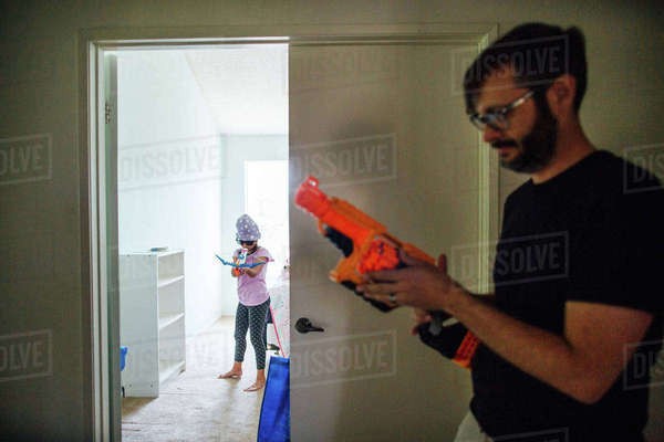 Father and daughter playing with toy guns at doorway Royalty-free stock photo