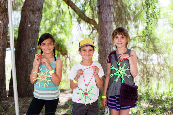 Portrait of siblings holding star shaped art work while standing against trees Royalty-free stock photo
