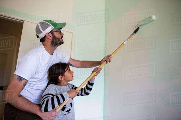 Father helping daughter in painting wall with paint roller at home Royalty-free stock photo