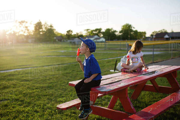 Siblings eating flavored ice while sitting on picnic bench at park Royalty-free stock photo