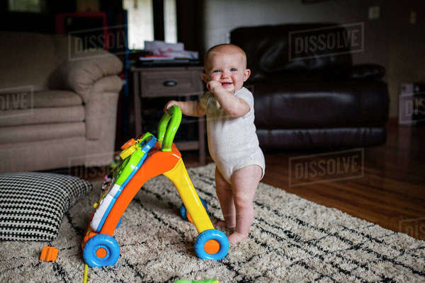 Portrait of happy baby girl with walker standing on rug at home Royalty-free stock photo
