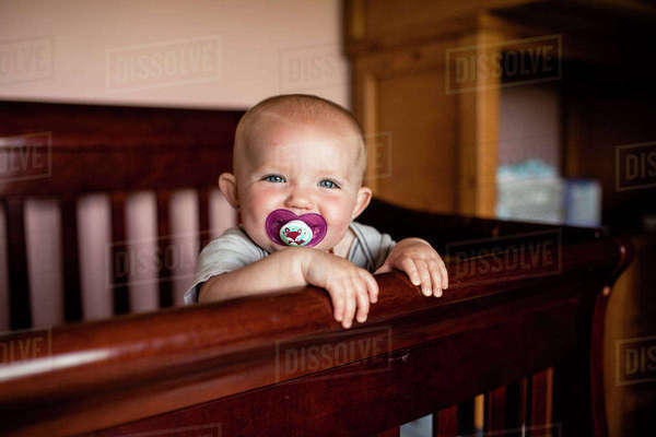 Portrait of happy baby girl sucking pacifier while standing in crib Royalty-free stock photo