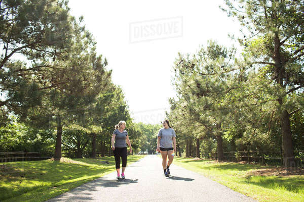 Mother and daughter in sportswear walking on footpath at park during sunny day Royalty-free stock photo