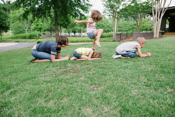 Mother and children playing leapfrog at park Royalty-free stock photo