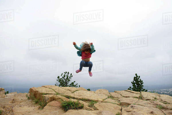Full length of girl jumping on mountain cliff against sky at Custer State Park Royalty-free stock photo