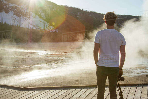 Rear view of hiker looking at steam coming out from hot spring at Yellowstone National Park Royalty-free stock photo