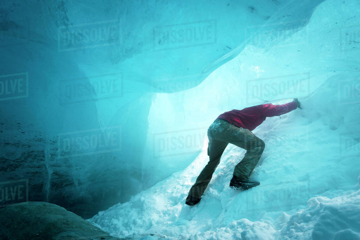 Low angle view of hiker ice climbing in cave Royalty-free stock photo
