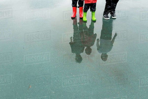 Low section of friends reflecting while standing on wet city street during rainy season Royalty-free stock photo