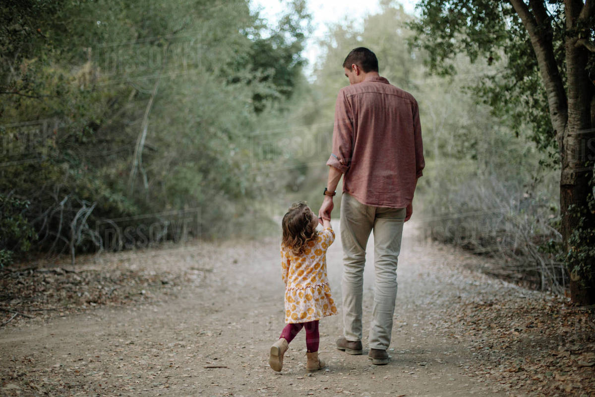 Rear View Of Father And Daughter Holding Hands While Walking On Dirt