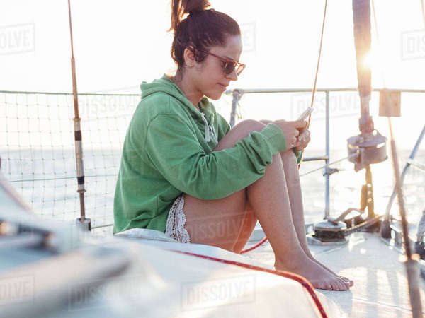 Full length of woman using smart phone while sitting in sailboat against clear sky Royalty-free stock photo