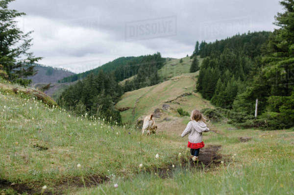 Rear view of girl walking on grassy field with dog against hills Royalty-free stock photo