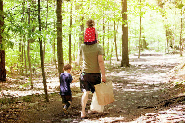 Rear view of father holding bags with son and daughter walking on dirt road amidst forest Royalty-free stock photo