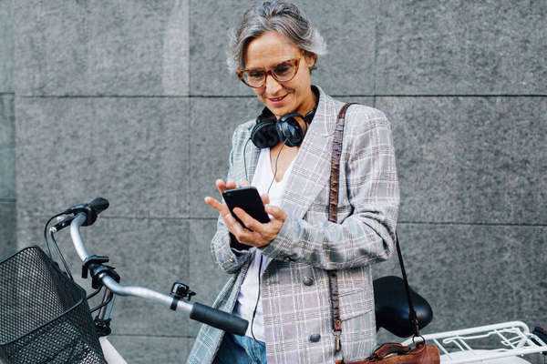 Happy woman in jacket using smart phone while standing against wall Royalty-free stock photo