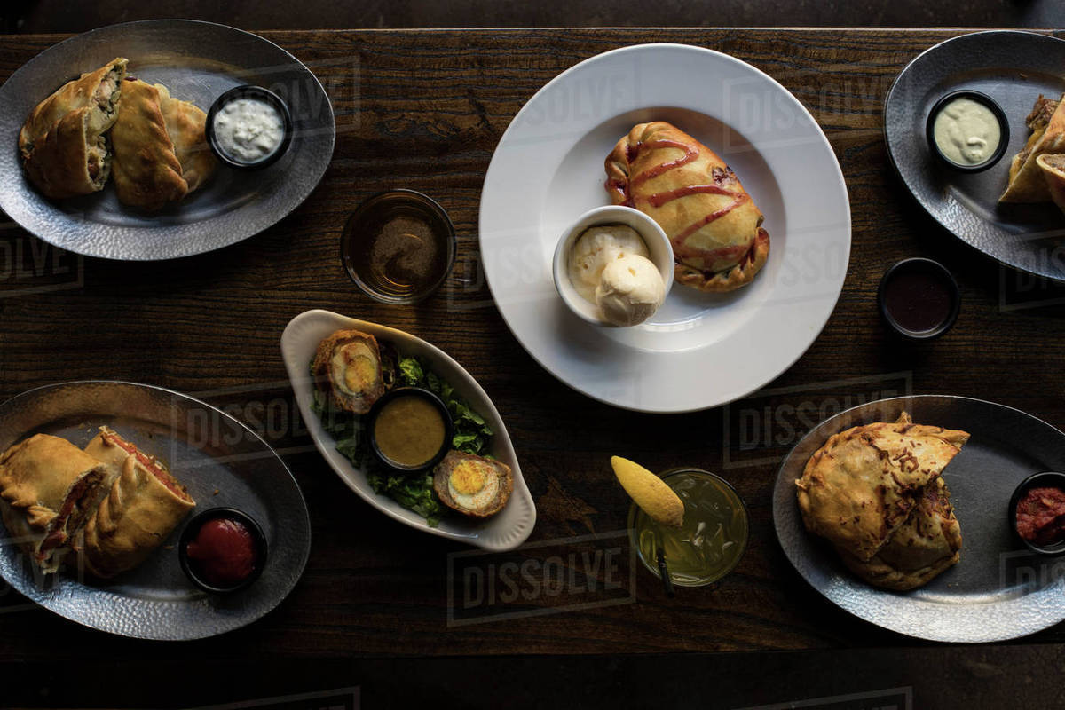 Overhead View Of Food In Plates On Dining Table At Restaurant
