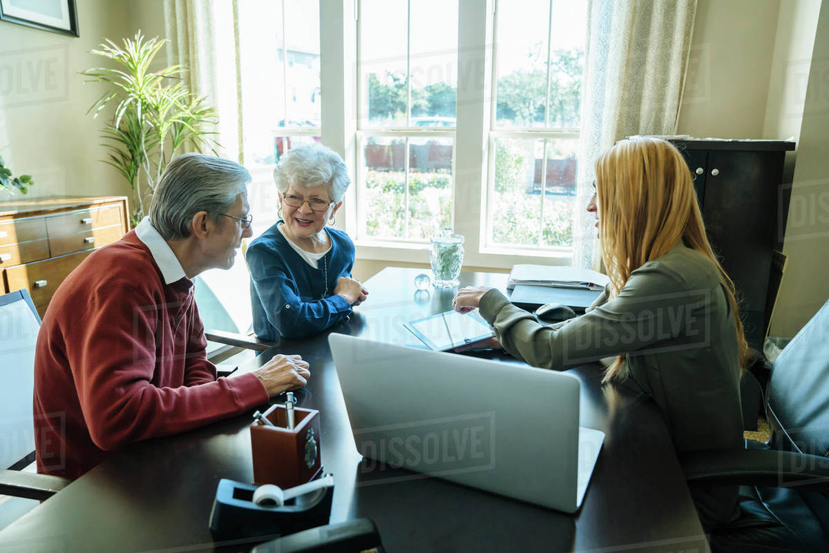 Financial Advisor Explaining Plan To Senior Couple On Tablet Computer While  Sitting In Office