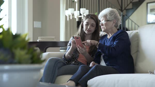 Handheld shot of granddaughter showing smart phone to grandmother while sitting on sofa at home Royalty-free stock video