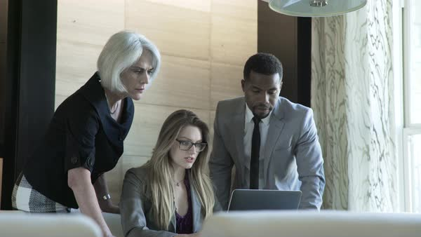 Handheld shot of businesswoman explaining colleagues over laptop computer in board room Royalty-free stock video