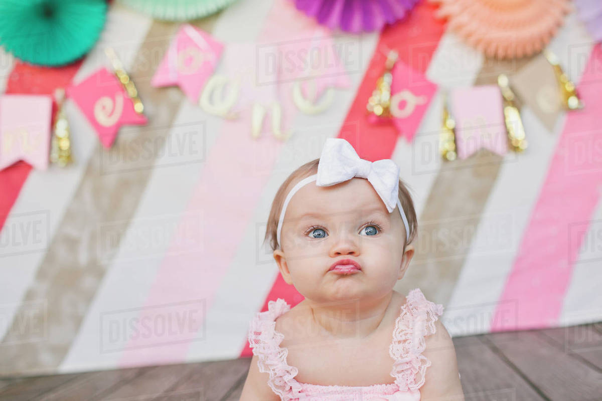 cute baby girl puckering against decoration at her first birthday