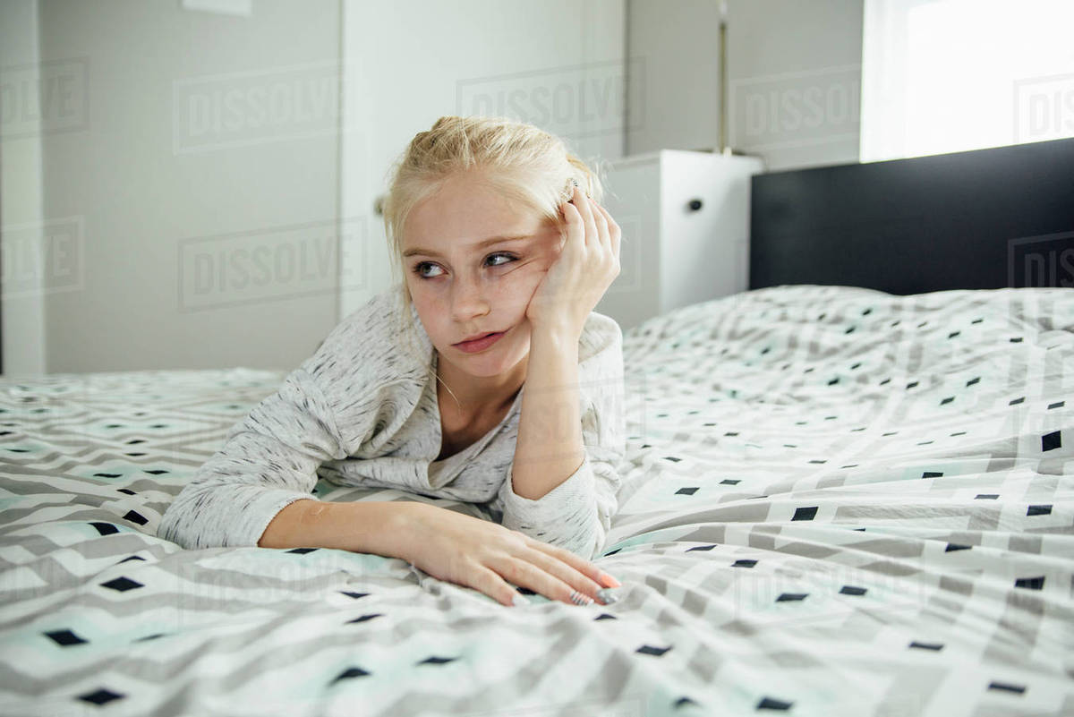 Bored girl looking away while lying on bed at home - Stock Photo ...
