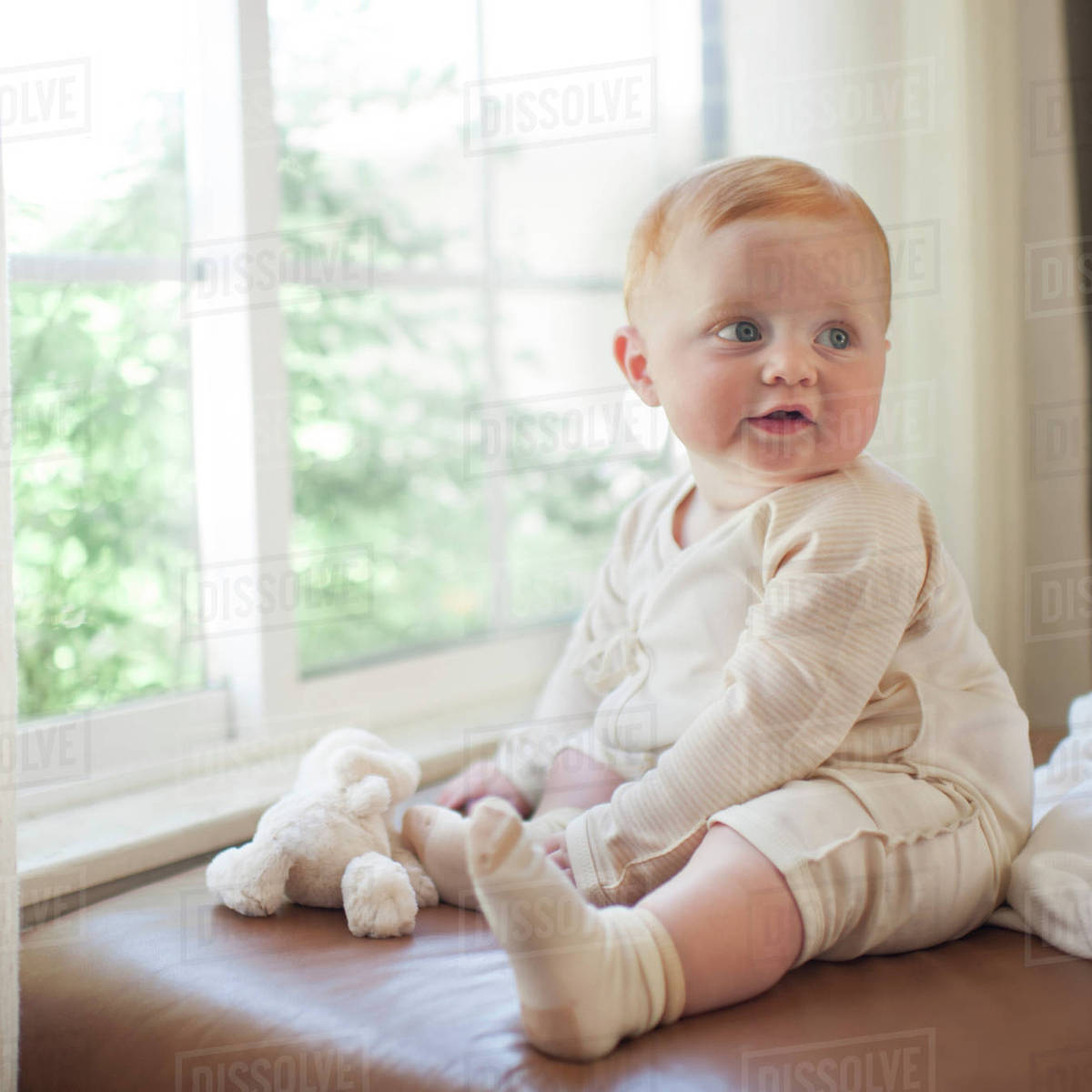 cute baby boy looking away while sitting on sofa against window