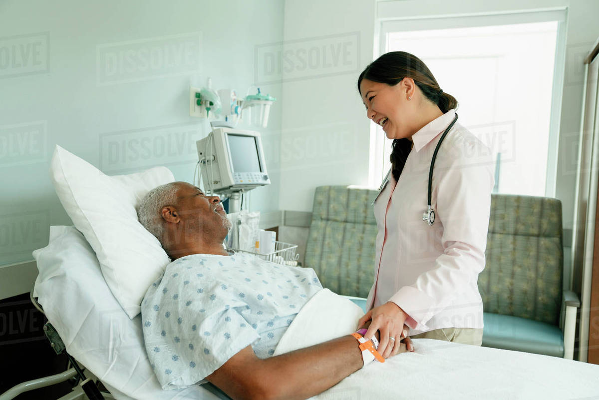 Cheerful Doctor Talking With Senior Patient Lying On Bed In Hospital