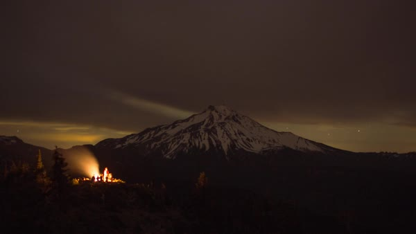 Timelapse shot of campfire burning on cliff by snowcapped mountain against star field Royalty-free stock video