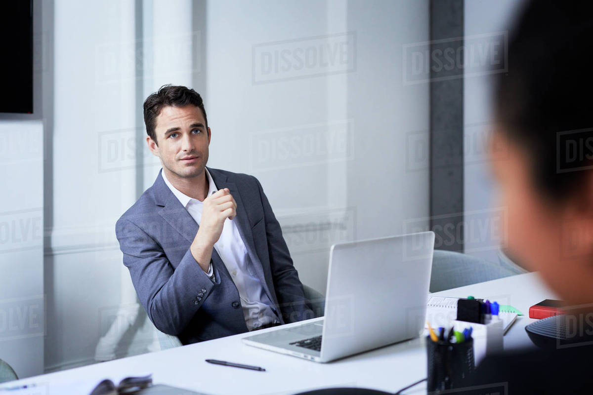 office meeting. Businessman Listening To Coworker At Conference Table In Office Meeting N