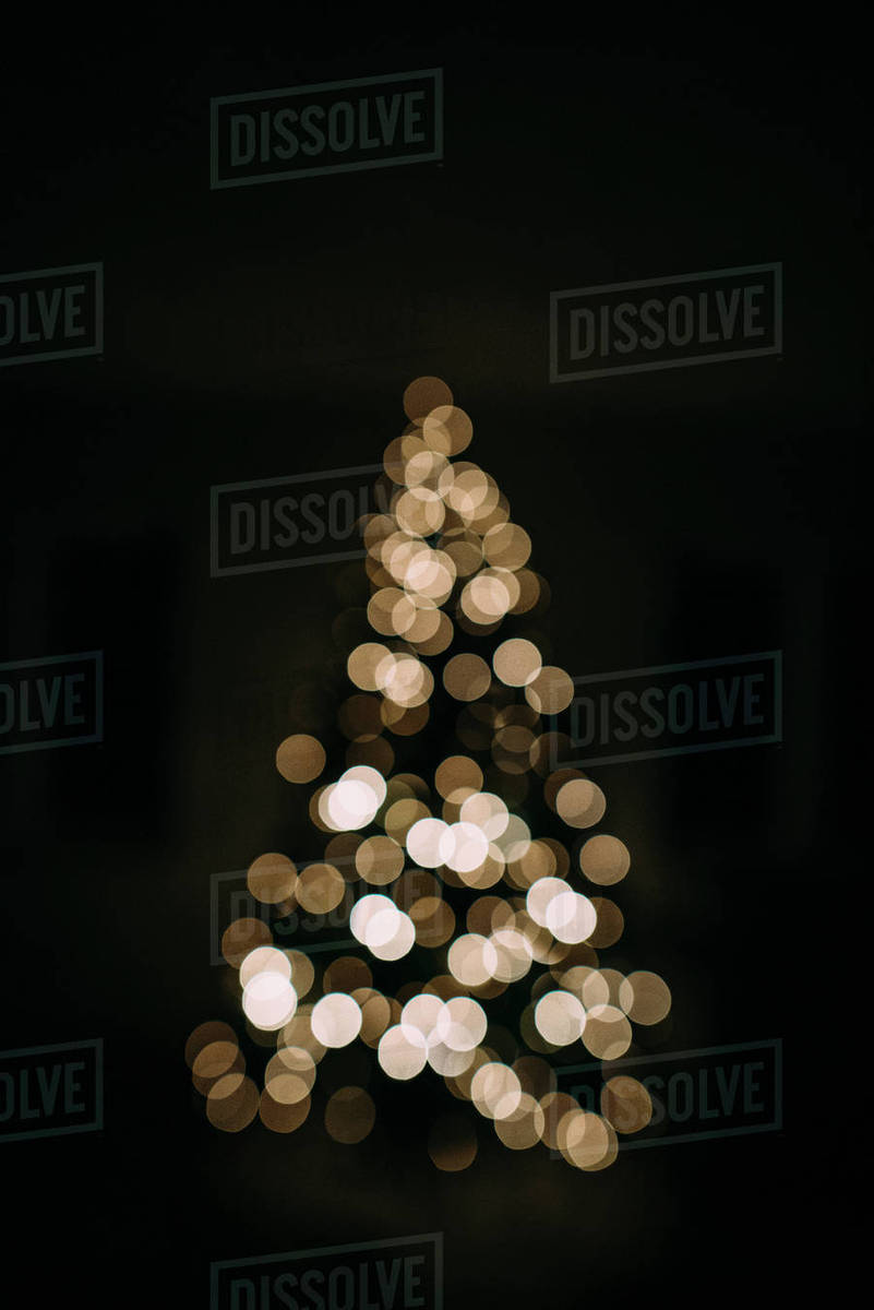 At Home Christmas Trees.Defocused Image Of Illuminated Christmas Tree In Darkroom At Home Stock Photo