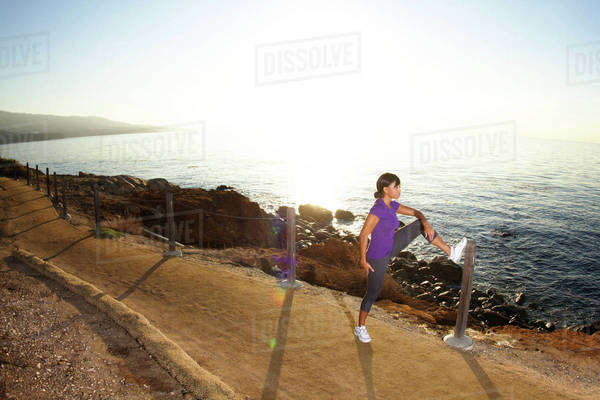 Female jogger stretching on ocean path Royalty-free stock photo