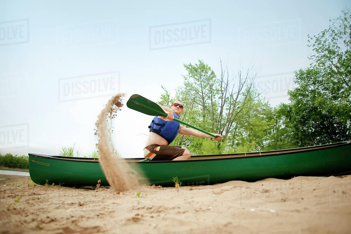 Man paddling canoe on beach by Hudson River Royalty-free stock photo