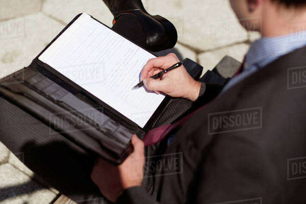 Young businessman writing in notebook Royalty-free stock photo