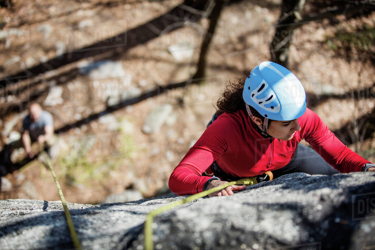 Young woman climbing up cliff Royalty-free stock photo