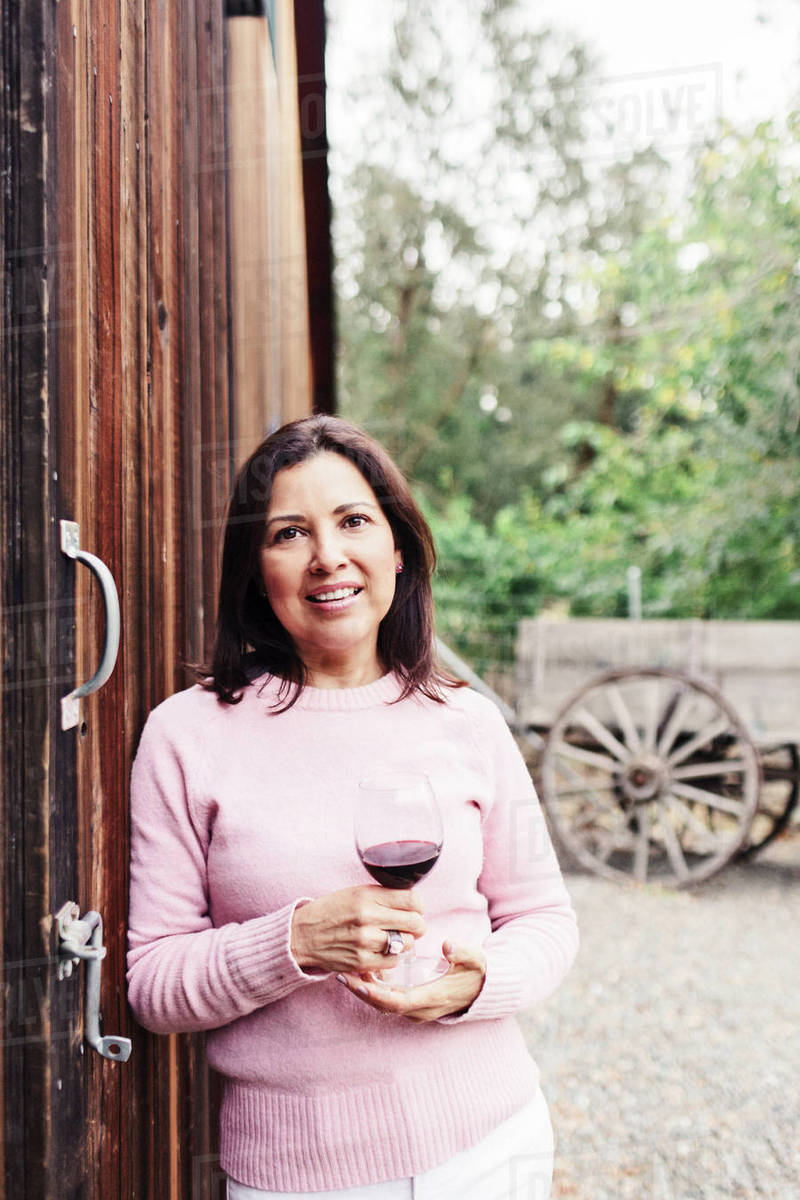 Portrait of confident mature woman with red wine standing by barn stock  photo